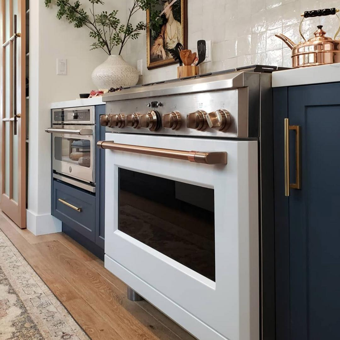 Blue cabinets and matte white range